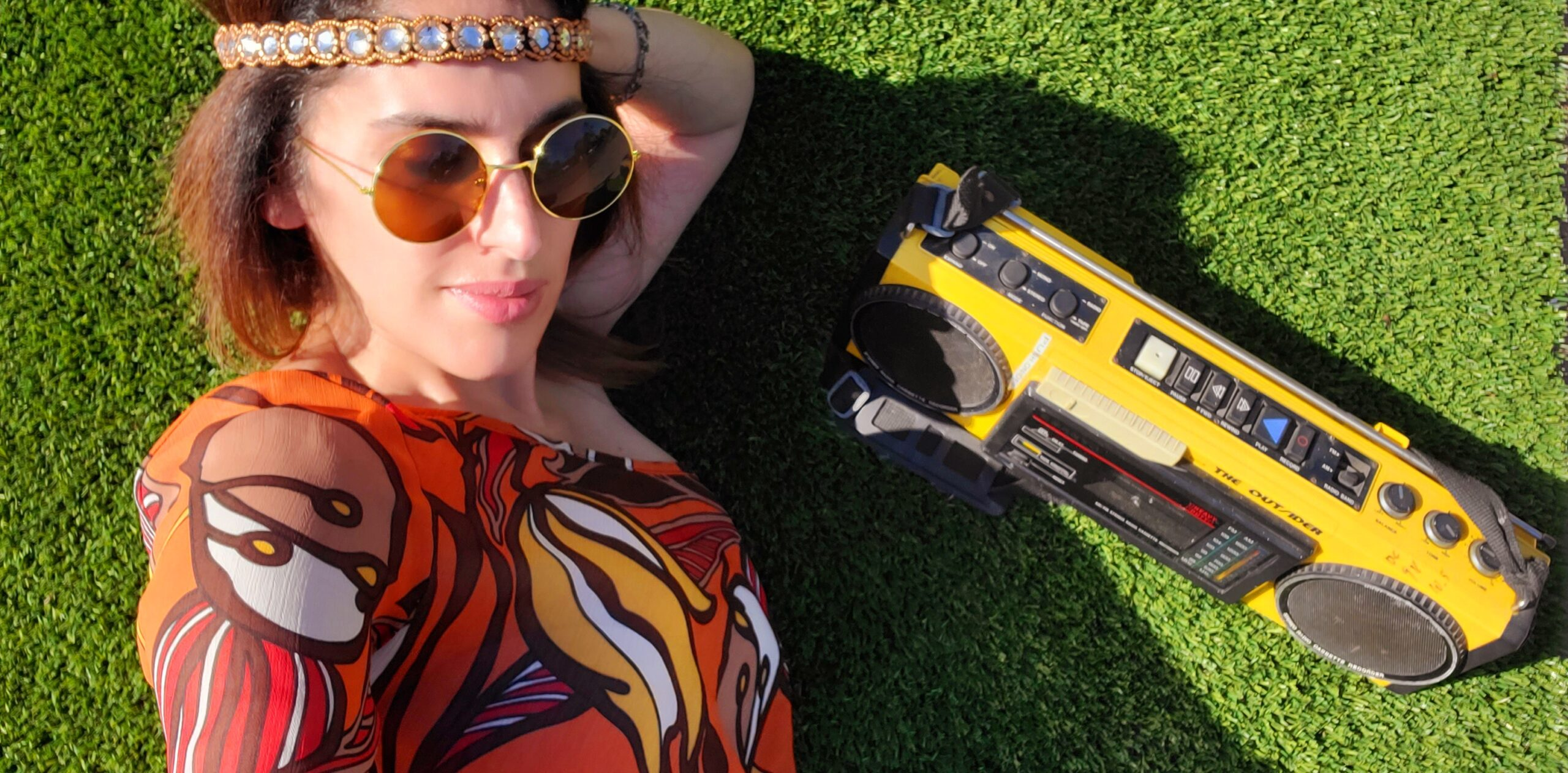 girl sitting on the green grass with radio cassette yellow